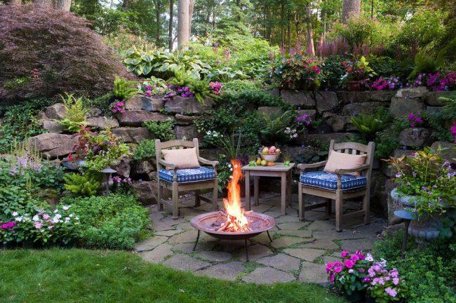 Уютное патио в саду с красивым ландшафтным дизайном и обилием цветущих растений