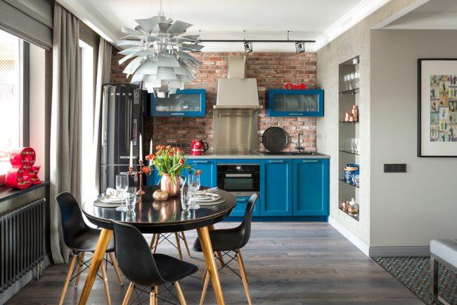 Синие кухонные шкафы на фоне кирпичной кладки смотрятся очень интересно