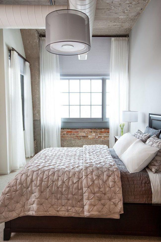 Светло-серые жалюзи и белая легкая тюль хорошо сочетаются в небольшой спальне индустриального стиля