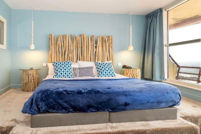 Для спальни морской тематики подойдут голубые шторы по длине окна