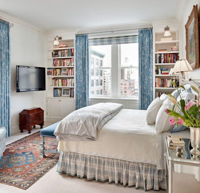 Классические голубые шторы с рисунком в сочетании с римскими шторами в уютной светлой спальне