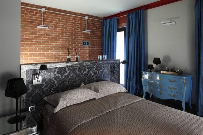 Для спальни в стиле лофт с коричневой кирпичной стеной идеально подойдут темные синие шторы из тафты
