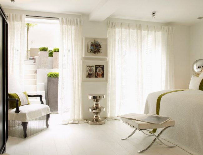 Классические белые ажурные шторы красиво смотрятся в светлой спальне средиземноморского стиля