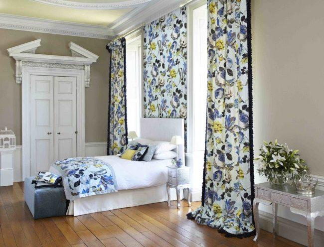 Анлийский стиль в оформлении спальни с цветными шторами, которые поддержаны вставкой из обоев с тем же рисунком и таким же покрывалом
