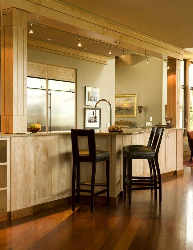 Объединенная с кухонным гарнитуром барная стойка на современной кухне. Шинная система освещения со светильниками с поворотной функцией, установленная над поверхностью