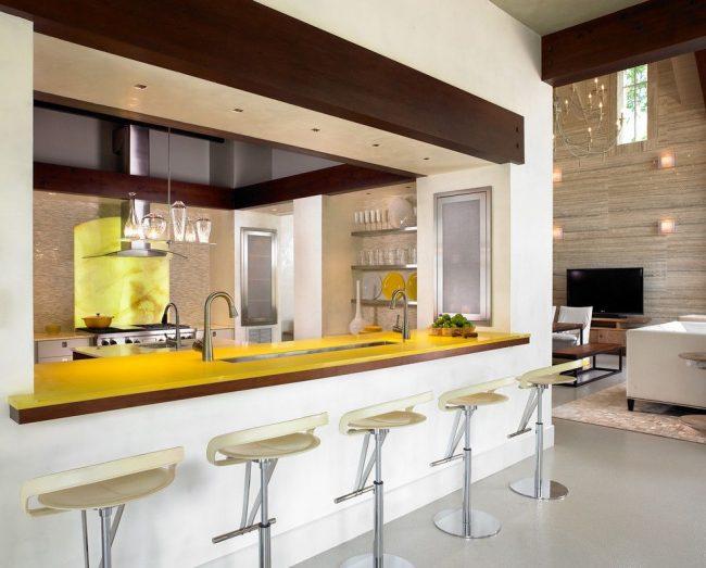 Яркая желтая столешница барной стойки выполнена из пластика. Пластик – современный материал, беспроигрышно подходящий для кухонь в стиле хай-тек и минимализм
