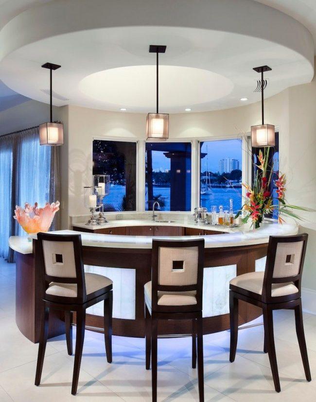 Пример правильной конфигурации на кухне современного стиля: барная стойка, состоящая из двух частей образующих овал; высокие стулья и центральная стена с окнами повторяющие форму; круглый подвесной потолок