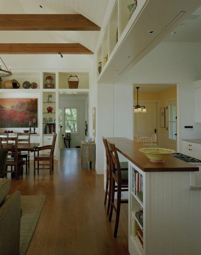Кухня в классическом стиле с деревянной барной стойкой. Пристенная конфигурация конструкции. Точечные светильники над обеденной зоной стойки встроенные в консоль
