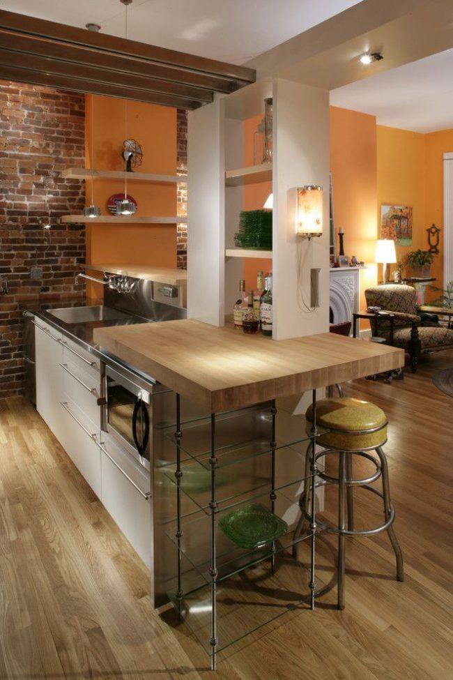 Кухонный остров оригинальной конструкции. Барная стойка состоит из обеденной зоны и дополнительного рабочего места. Деревянная столешница для обеденного места и металлическая для рабочего. Так же конструкция включает функциональную гипсокартонную нишу с полками