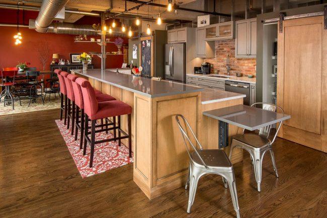 Кухня в индустриальном стиле с металлическими, бетонными и кирпичными элементами. Шинная конструкция освещения с ретро-лампочками Эдисона