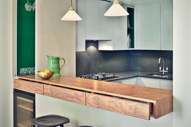 Современная кухня с фасадом из пластика и столешницей из дерева среднего тона. Стеклянная консоль с выдвижными полками для хранения. Особенность барной стойки в выдвижных ящиках, встроенных в столешницу