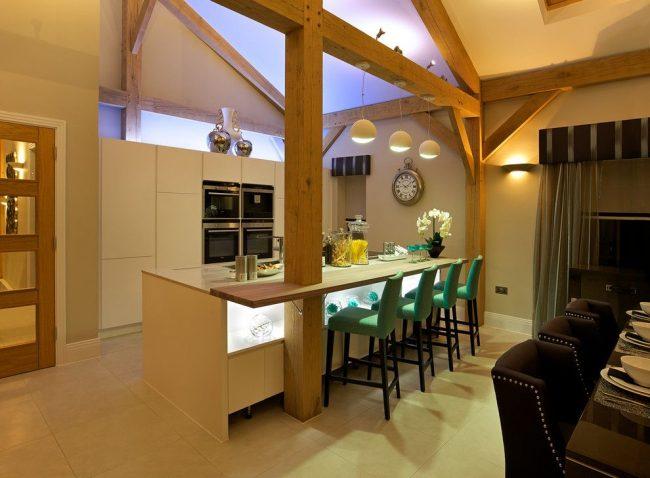 Стиль модерн для лондонской кухни. Подсветка, встроенная в фасад основания барной стойки – один из видов освещения. Второй вид – подвесные лампы над поверхностью
