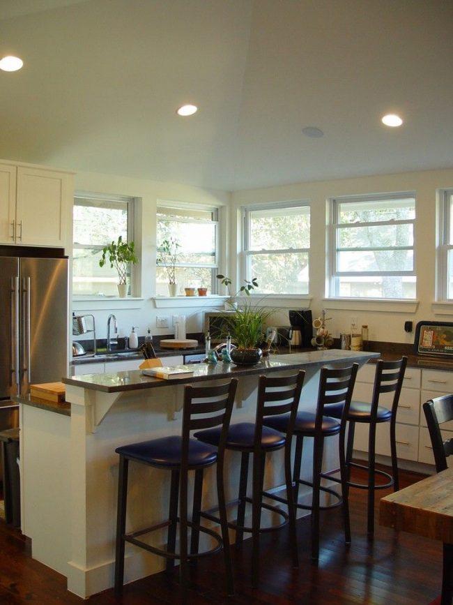Барная стойка для кухни двухуровневой конструкции. Одна половина, высокая, выполняет функции обеденного стола, а другая – дополнительного рабочего места