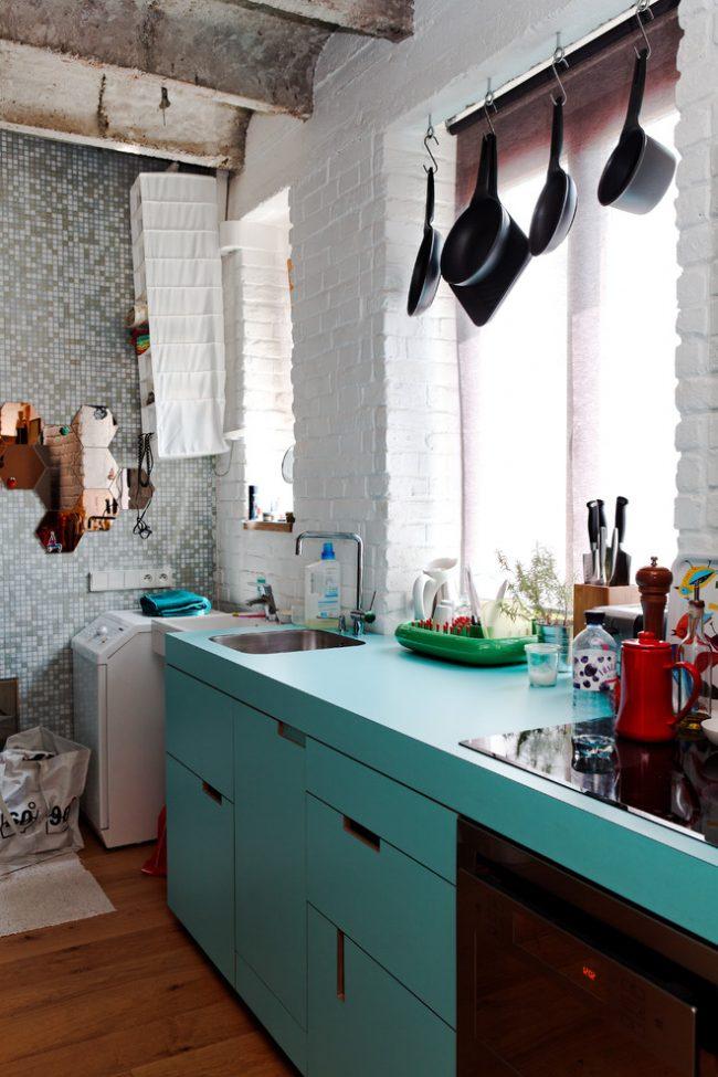 Отдельно стоящая стиральная машина с вертикальной загрузкой, установленная в углу кухни
