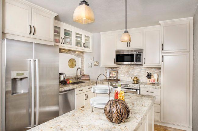 Что бы кухня не казалась стерильно белой, нужно внести один или несколько ярких акцентов в интерьер. Привнести цвет в интерьер можно с помощью системы освещения, напольного покрытия, каменных или деревянных столешниц