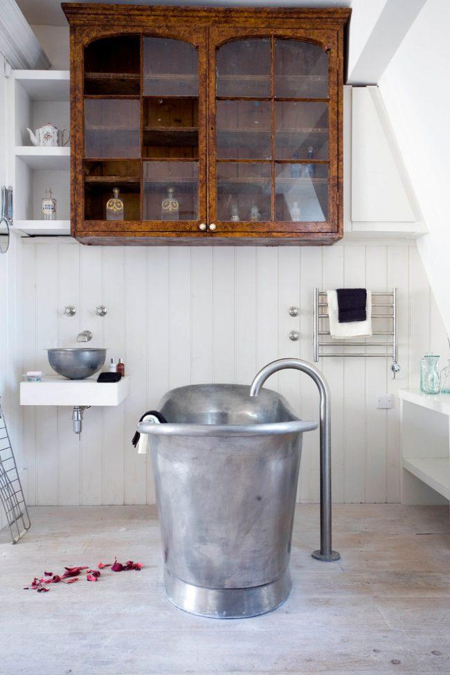 Навесной старинный шкафчик из дерева в интерьере светлой ванной комнаты