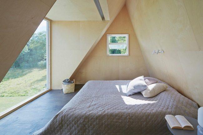 Небольшая спальня в мансардной комнате треугольного домика