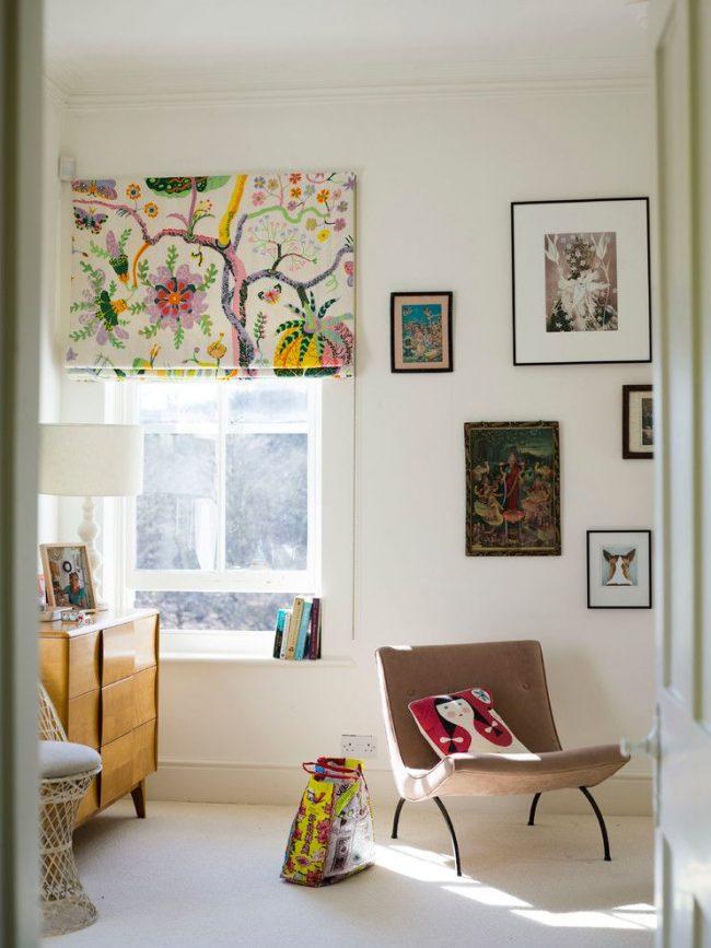 Светлая комната, наполненная яркими декоративными элементами. Плотные римские шторы с принтом крепятся с помощью классического типа держателя, настенного, и оснащены автоматическим типом управления