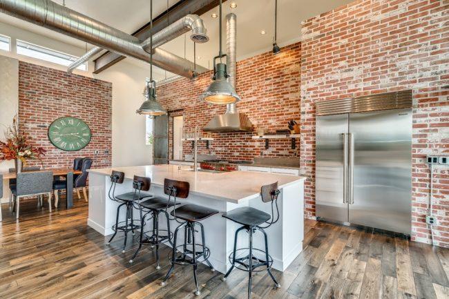 Великолепное сочетание кирпичной стены с дизайнерской меблировкой и современным декором кухни