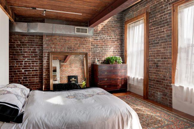 Спальня с кирпичными стена с индустриальным мотивом