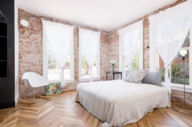 Кирпичные стены в просторной спальне
