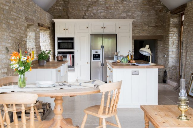 Крупная напольная плитка в светлой кухне с внутренней отделкой из камня