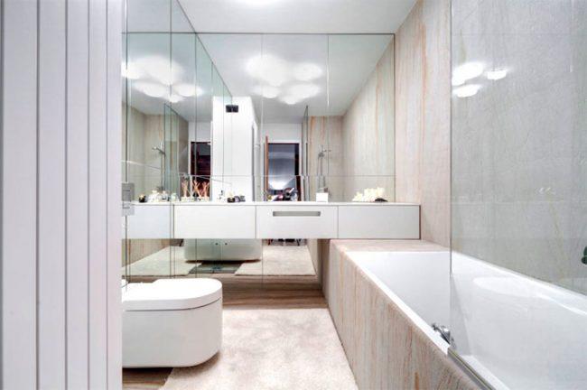 Зеркальная стена в тандеме со светлой отделкой зрительно увеличивает помещение