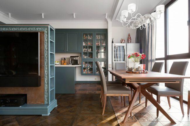 Пример сочетания близких цветов в рамочных фасадах классической кухни, собранной из модулей, и мебели в гостиной-студии