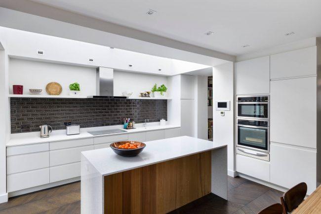 Современный дизайн кухни без верхних шкафов и с островом: древесный рисунок и белый цвет фасадов без ручек и фартук из черной плитки-метро