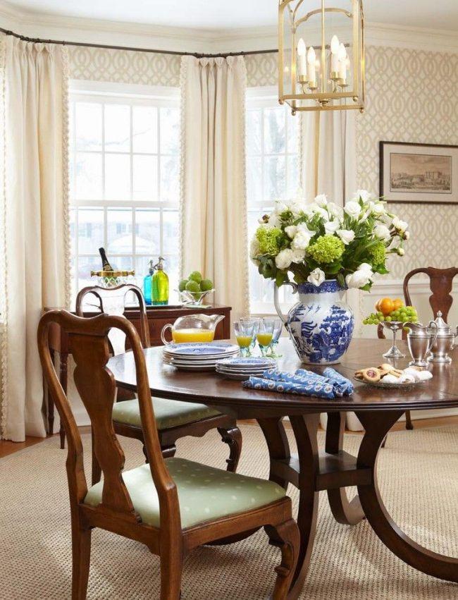 Изысканное оформление интерьера: сочетание светлых обоев с деревянными элементами. Деревянный круглый обеденный стол со стульями, деревянный карниз и рама картины, деревянная тумба – обилие древесины в интерьере английского стиля
