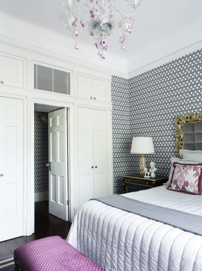 Спальная комната в георгианском стиле с четкими и симметричными деталями, но в тоже время и с цветочными интерьерными элементами. Пример: сочетание графических двухцветных обоев с классической люстрой, украшенной цветочными подвесками