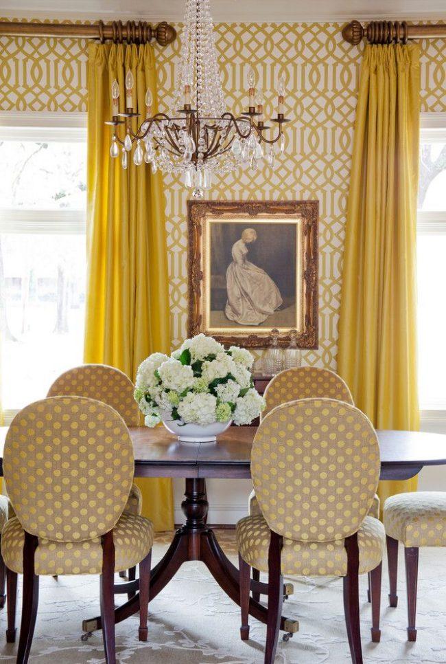 Бежево-желтые обои в столовой английского стиля. Особенность интерьера в ярком текстиле, классической живописи в металлической раме, деревянном обеденном месте