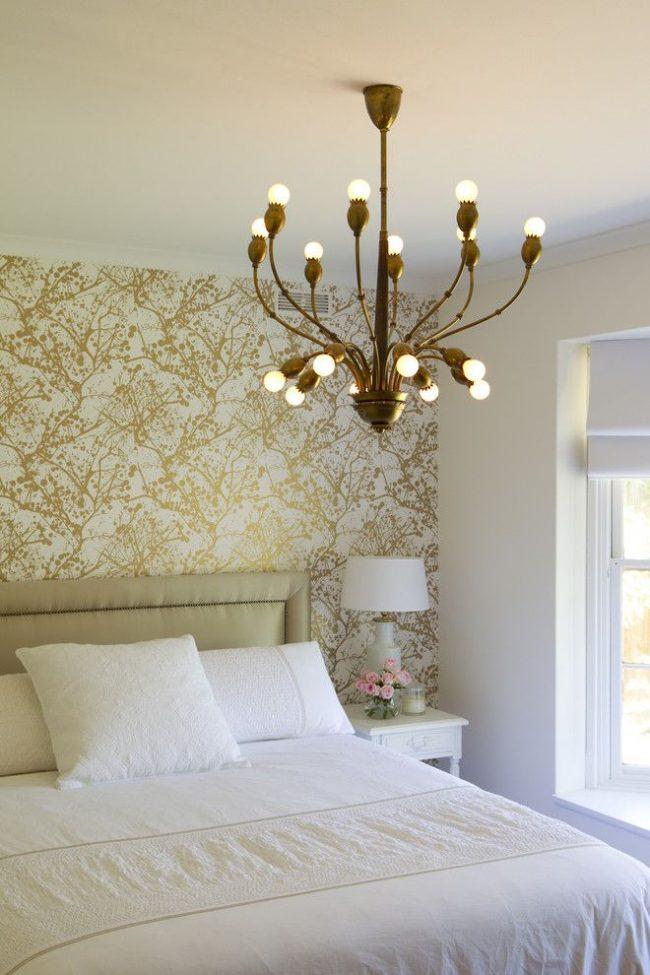 Изысканная спальня: общее оформление в белом цвете, обои английского стиля с хаотичными золотыми узорами над спальным местом, оригинальная люстра бронзового цвета