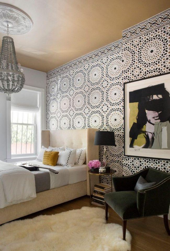 Бумажные обои с орнаментом для спальни в английском стиле. Особенности интерьера: потолочная розетка с классической люстрой, римские шторы на окнах, портрет в стиле Энди Уорхола, классическое кресло с бархатной обивкой и другие элементы