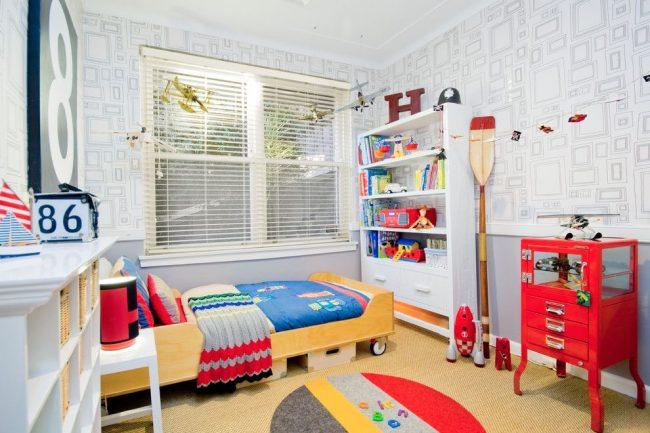 Нейтральные светлые обои в сочетании с яркими и оригинальными интерьерными элементами: желтая кровать на колесах, красная тумбочка, подвешенные модели самолетов, разнообразный текстиль, множество игрушек и т.д.