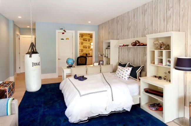 Зонирование комнаты с помощью окраса обоев: фотообои с древесной имитацией для зоны отдыха и светло-голубой оттенок обоев для общего пространства