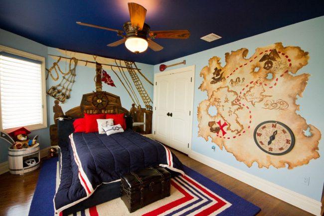 Сине-голубая цветовая гамма с вкраплениями коричневого и бежевого цветов для оформления детской комнаты в пиратском стиле. Штурвал и карта сокровищ, изображенные на стенах – ручная роспись
