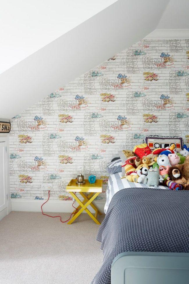 Комната для мальчика в стиле минимализм светлой цветовой гаммы. Яркие мелочи задают настроение: надписи на обоях, желтая прикроватная тумбочка, голубой будильник, множество мягких игрушек