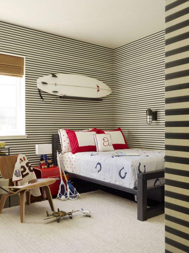 Полосатые обои для комнаты мальчика-подростка в свежем пляжном стиле. Доска для сёрфинга, модели самолетов и другие предметы увлечений уверенно занимают свои места в интерьере