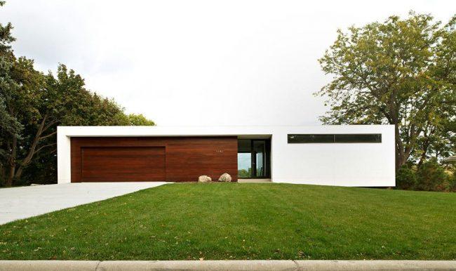 Экстерьер одноэтажного дома с пристроенным к нему гаражом выполнен в лаконичном стиле модерн
