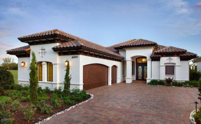 Дом со встроенным гаражом в двухцветной гамме. Общая территория большая и включает в себя заезд для авто