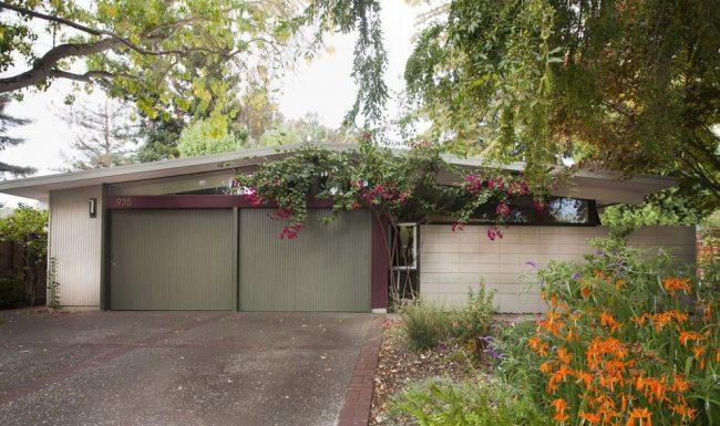 Размещенный на ровном ландшафте гараж, совмещенный с домом, имеет крышу двускатной конструкции
