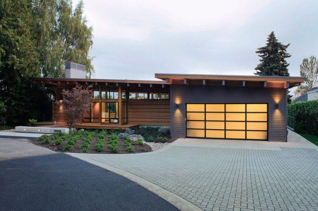 Одноэтажный дом с гаражом имеют самую простую и распространенную форму, прямоугольную. Для эстетики двери гаража выполнены из инновационного полупрозрачного материала с металлическими рамами