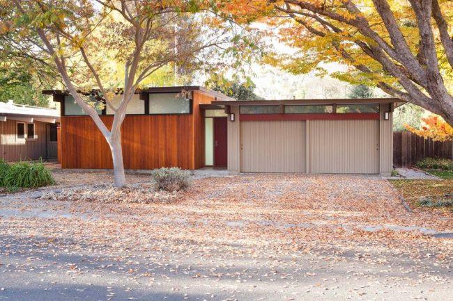 Одноэтажный дом с гаражом, стены, которых оформлены сайдингом, а крыша имеет плоскую конструкцию