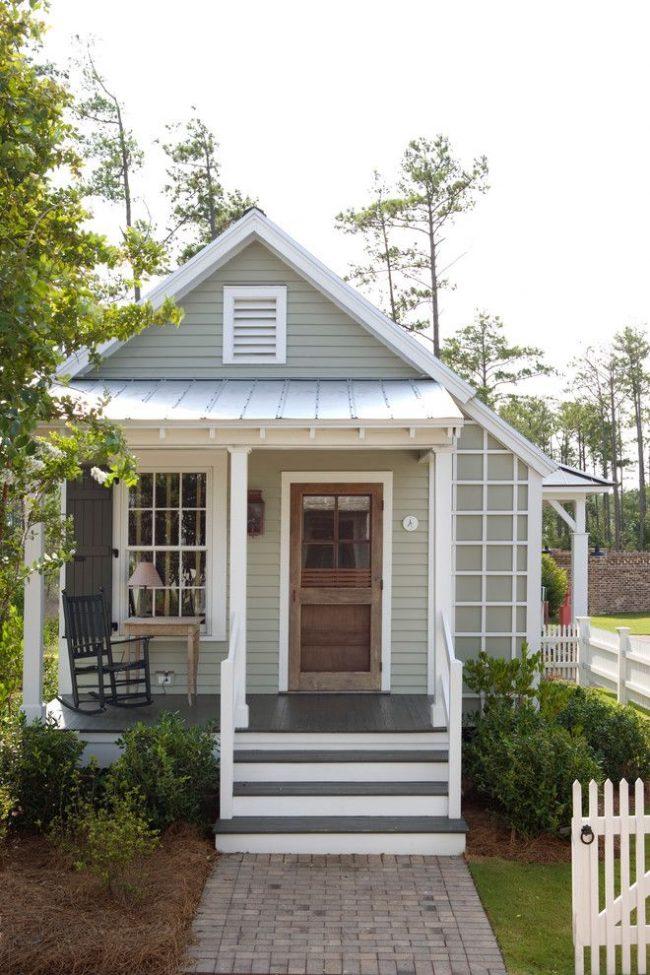 Компактный одноэтажный дом с небольшой террасой, совмещенной с крыльцом, зеленой придомовой территорией и гаражом с отдельным заездом