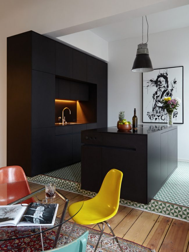 Матовый черный кухонный гарнитур и подсветка подвесных шкафов и рабочей поверхности желтоватым светом