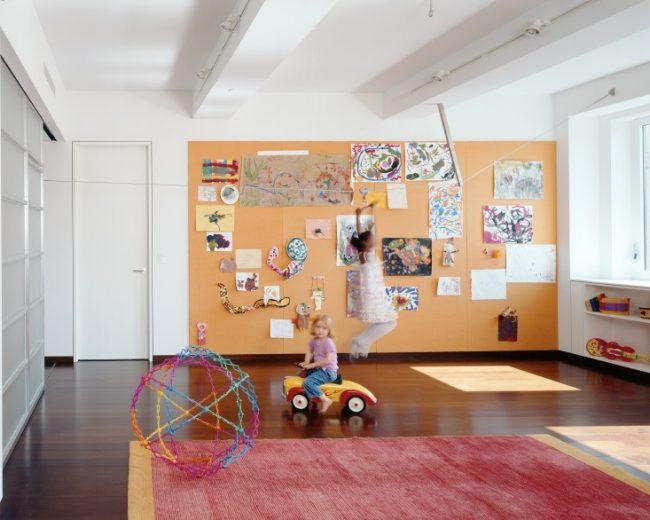 Просторная детская комната с выделенной стеной из пробкового материала