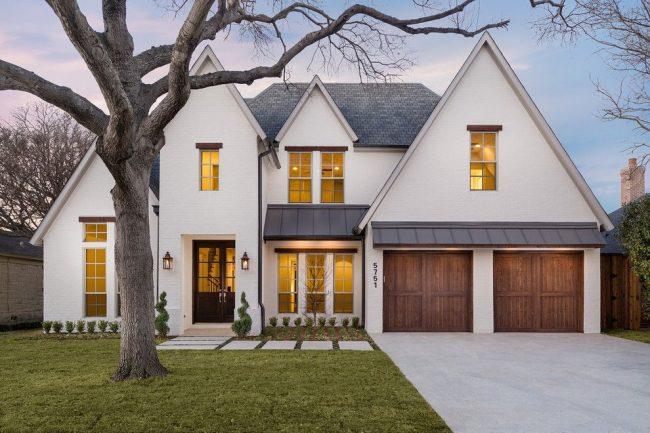 Двускатная крыша белого двухэтажного дома с двумя гаражами. Надежные плотно закрывающиеся деревянные двери гаражей – большой плюс при планировке