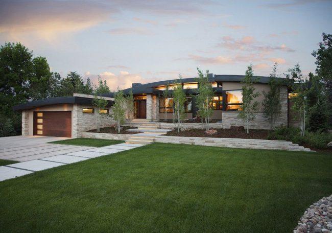 Современный экстерьер дома с гаражом: каменная облицовка, изогнутая крыша, яркое освещение, зеленая придомовая территория