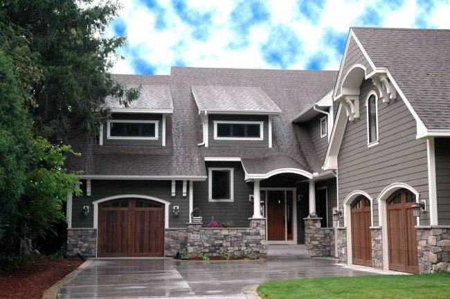 Цветной каменный фундамент, настенный деревянный сайдинг, черепичная крыша – отделка традиционного американского дома с гаражами. Особенность: размещение гаражей